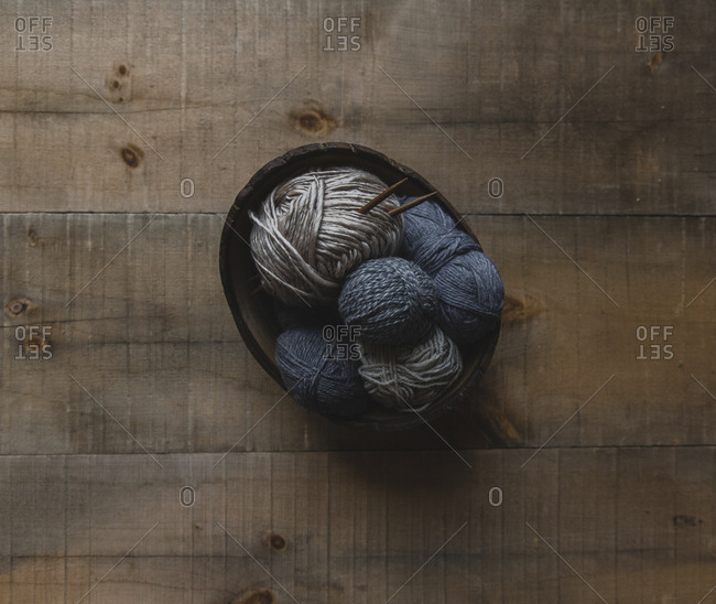 Overhead view of woolen balls in bowl on table