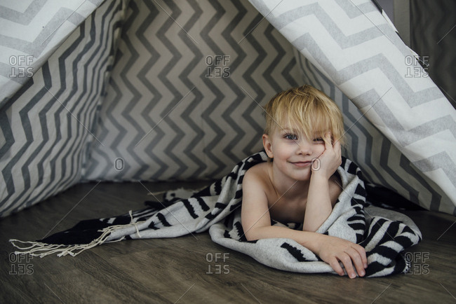 Portrait of boy with hand on chin lying in tent at home
