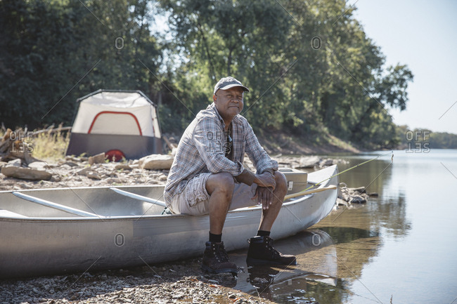 Portrait of man sitting on boat at lakeshore