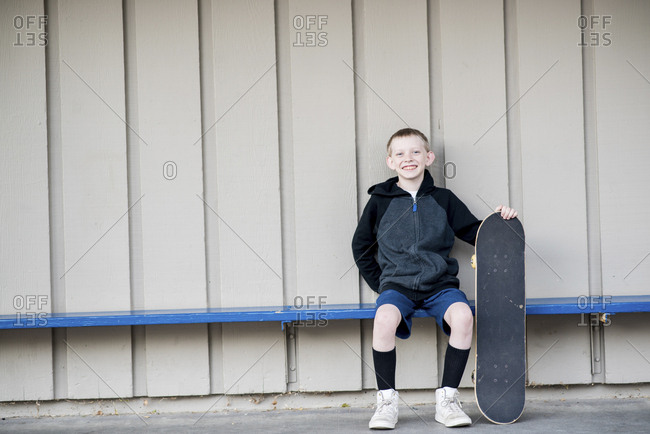 Portrait of smiling boy holding skateboard while sitting on bench against wall