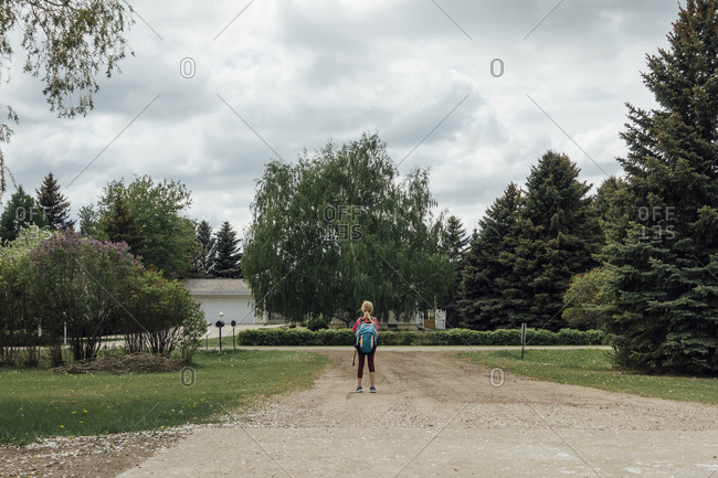 Rear view of girl with backpack standing on footpath against sky