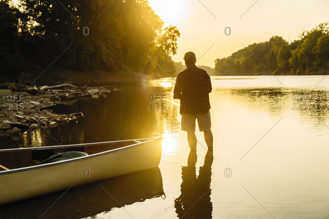 Rear view of mid adult man fishing while standing in lake during sunset