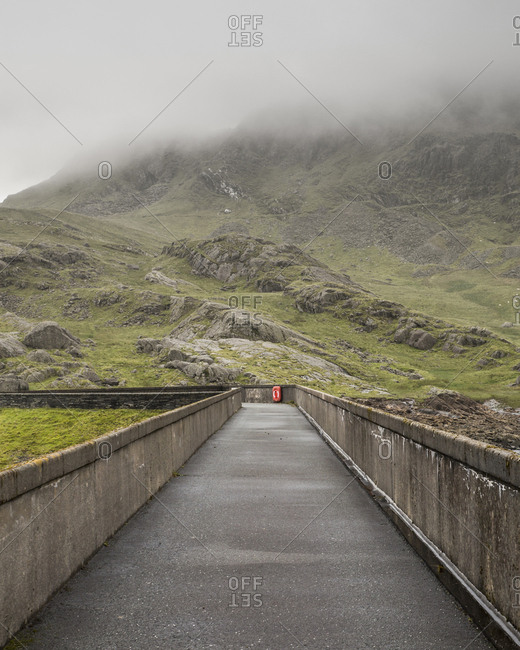 Scenic view of empty road amidst mountain during foggy weather