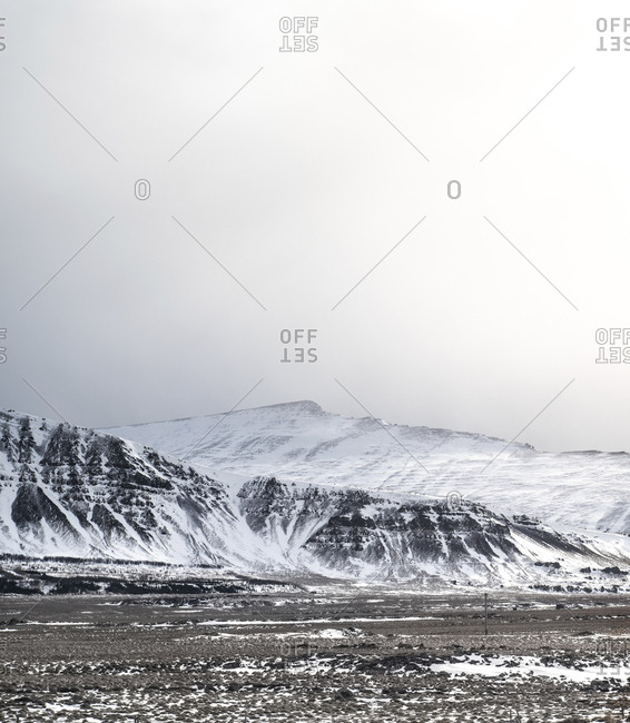 Scenic view of snowcapped mountains against sky during foggy weather