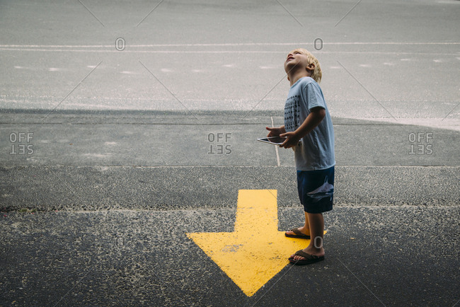Side view of boy with tablet computer looking up while standing by arrow symbol on road
