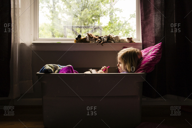 Side view of girl sitting in container by window at home