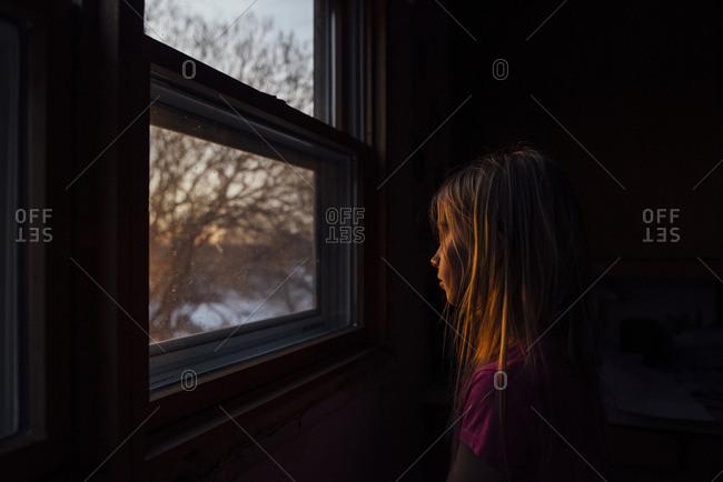Side view of girl sitting by window in darkroom