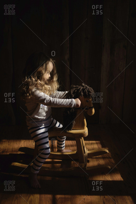 Side view of girl sitting on rocking horse at home