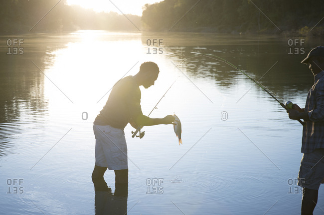 Side view of male friends fishing in lake during sunset
