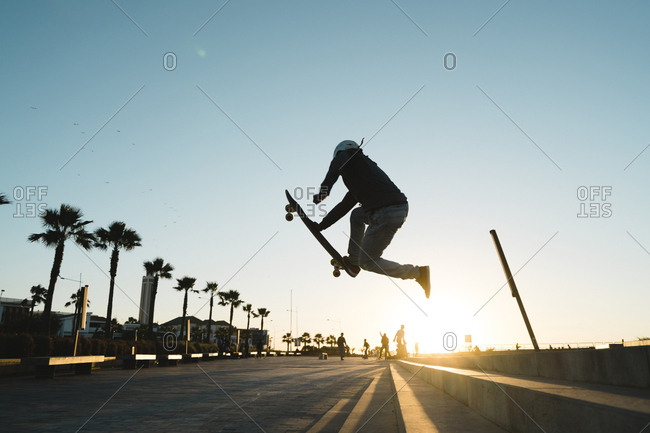 Side view of man performing stunt while skateboarding on road against sky