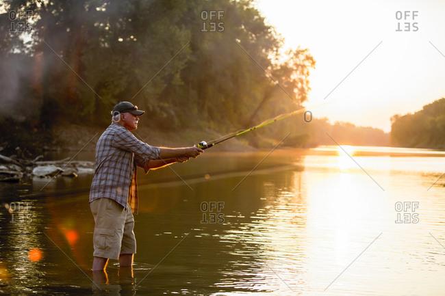 Side view of senior man fishing while standing in lake during sunset