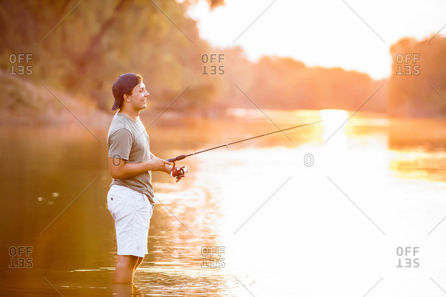 Side view of young man fishing while standing in lake during sunset