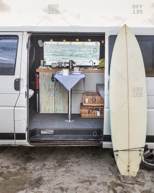 Surfboard by motor home parked at beach against sky