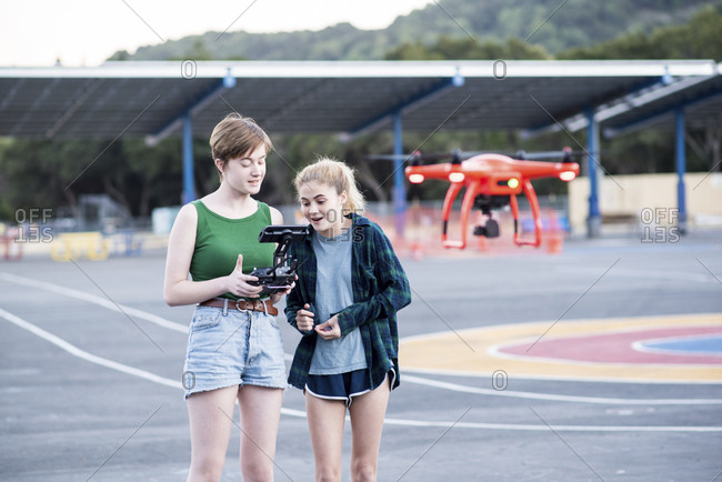 Teenage friends operating quadcopter at park