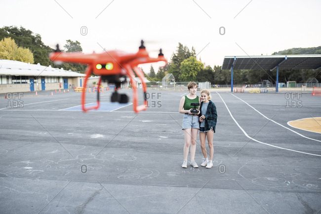 Teenage friends flying quadcopter at park