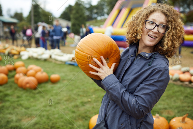 Woman holding pumpkin while standing at farm