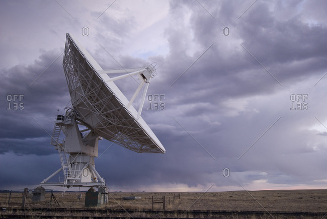 Satellite dish on field against cloudy sky