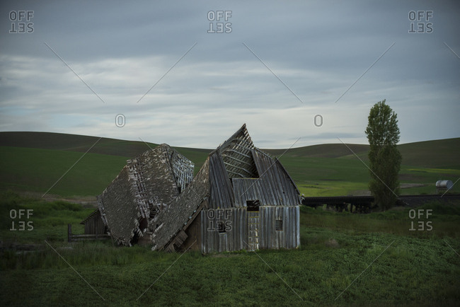 Abandoned house on field against cloudy sky at dusk