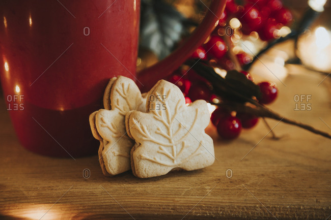 Cookies by coffee cup and Christmas decoration on table
