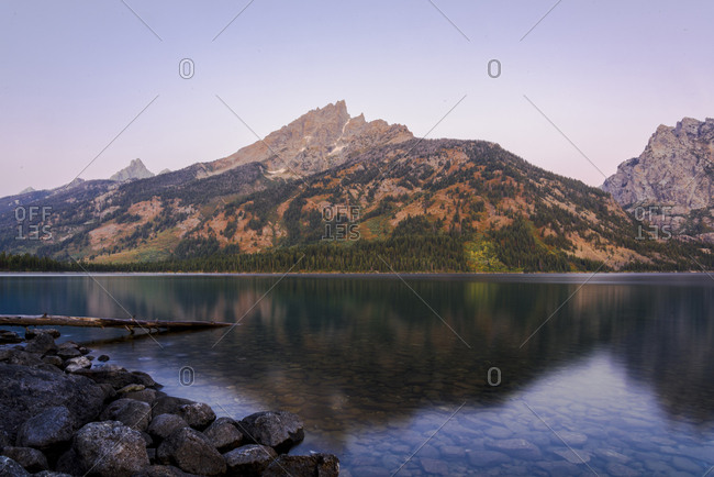 Scenic view of calm lake by mountains against clear sky during sunset