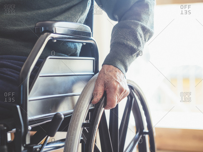 Close-up of man's hand on a wheelchair wheel