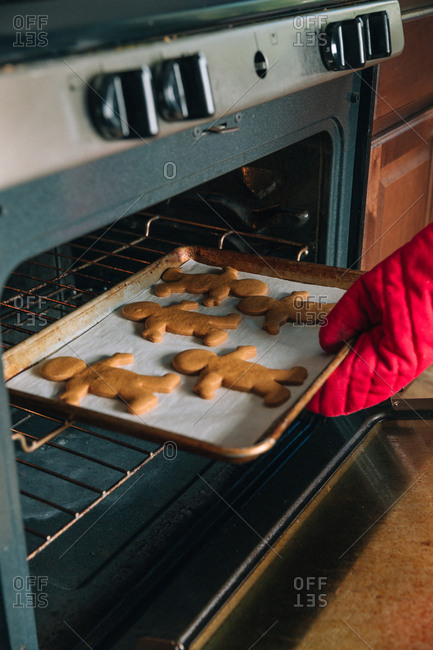 Woman removes fresh baked holiday cookies