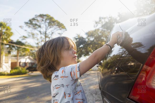 Boy helping polish the car