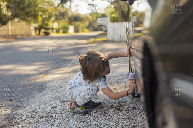 Little boy washing a car with a rag
