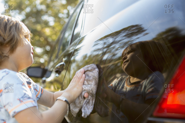 Reflection of little boy polishing a car with a rag