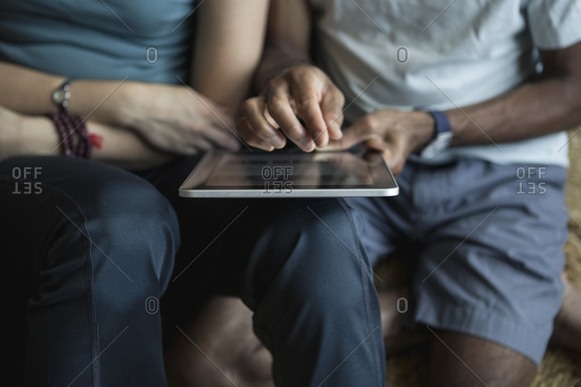 Midsection of multi-ethnic couple using digital tablet at home