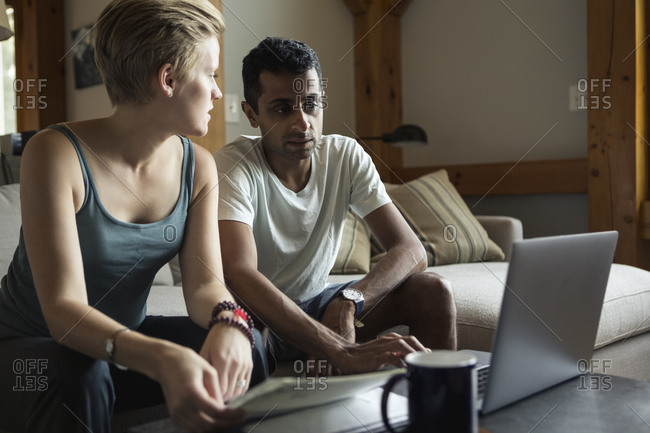 Mid adult couple using laptop to calculate home finance at home