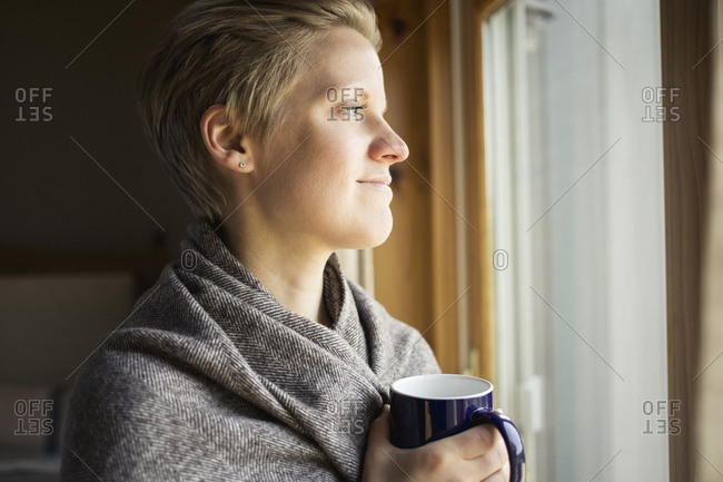 Mid adult woman wrapped in blanket having coffee while looking through window
