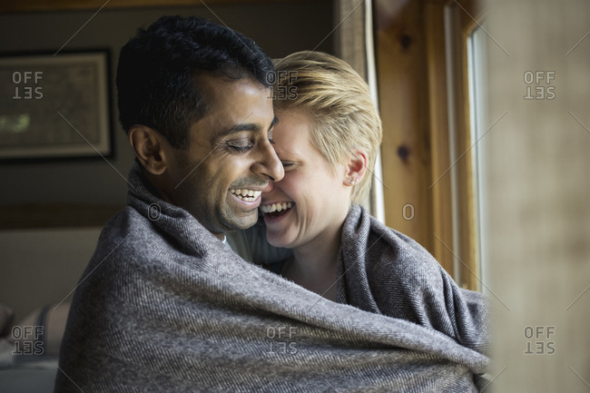 Smiling multi-ethnic couple wrapped in blanket and embracing at home