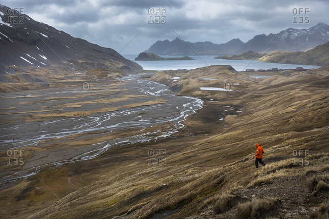 Stromness Harbor, South Georgia Island - November 16, 2016: Sir Peter Hillary hikes through remote terrain in the distance
