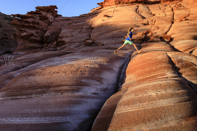 Puerto Gato, Baja California, Mexico - March 31, 2017: A girl leaps over cracks in a red sandstone formation on the Baja Peninsula, at Puerto Gato