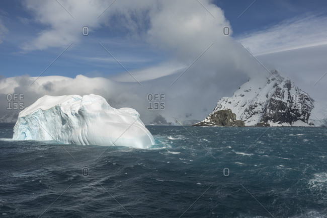Wind and waves surround a small iceberg
