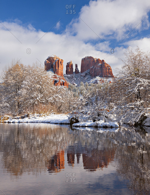 A winter snow blankets Sedona's iconic Cathedral Rock along Oak Creek