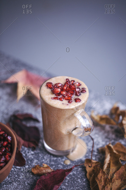 Banana almond butter smoothie topped with pomegranate seeds
