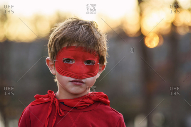 Portrait of a young boy wearing super hero cape and mask