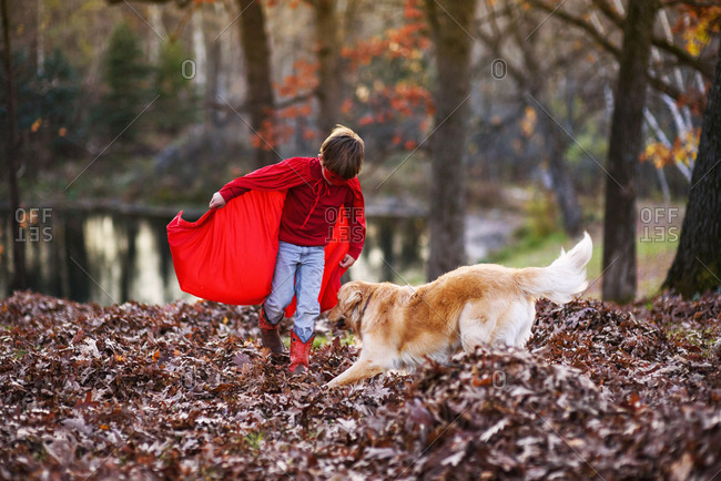 Young boy wearing super hero cape and mask playing with dog among autumn leaves