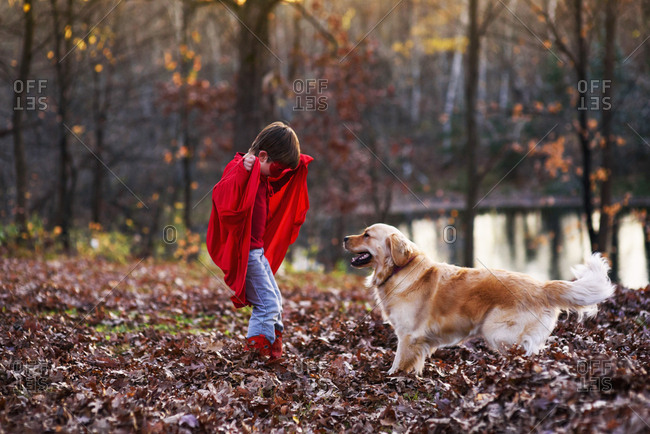 Young boy playing in the backyard with dog wearing super hero cape and mask