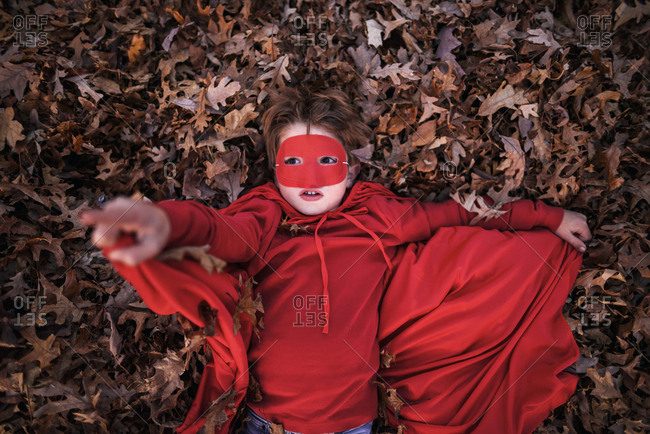 Young boy playing in the backyard wearing super hero cape and mask