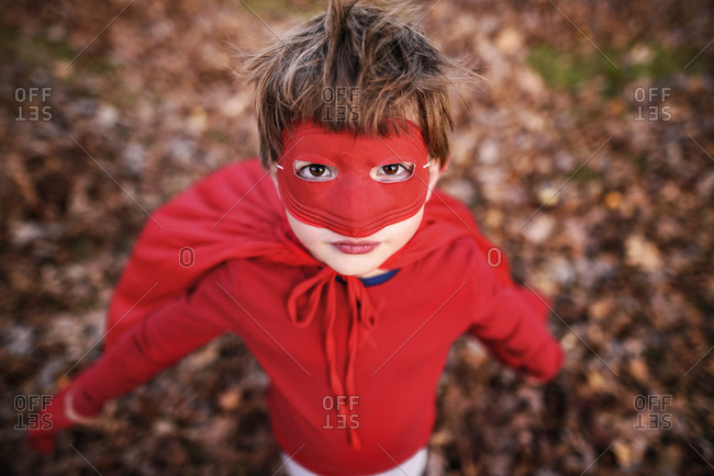 Portrait of a young boy playing in the backyard wearing super hero cape and mask