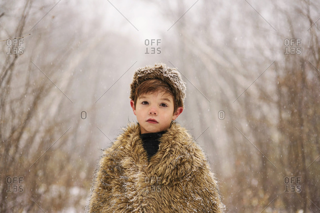 Portrait of a young boy wrapped in blanket in the snow