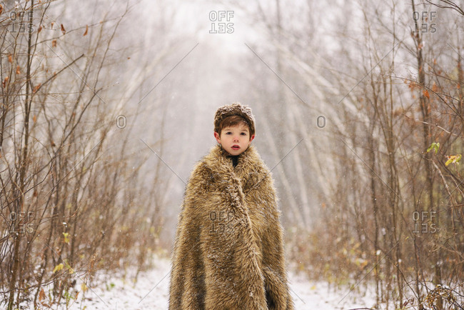 Young boy wrapped in blanket in the snow