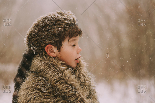 Portrait of a boy wrapped in a furry blanket in the snow