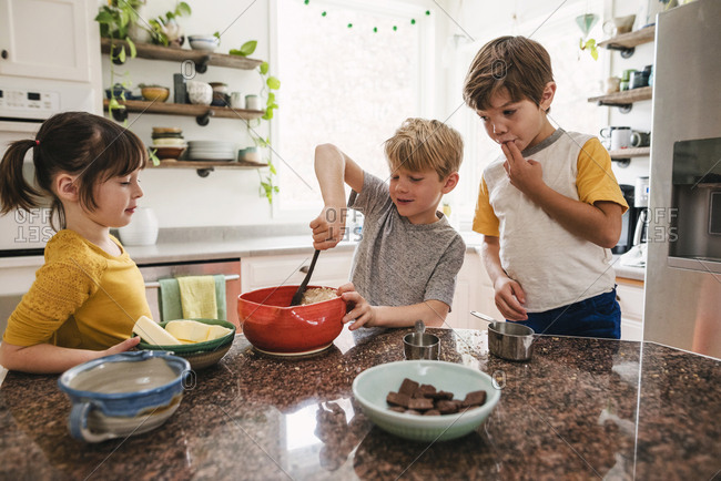 Three young children baking cookies together in the kitchen