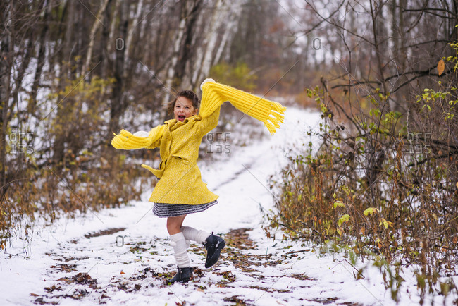 Young girl with long yellow scarf walking on winter trail