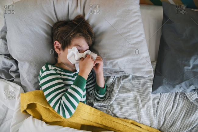Sick boy blows nose in bed