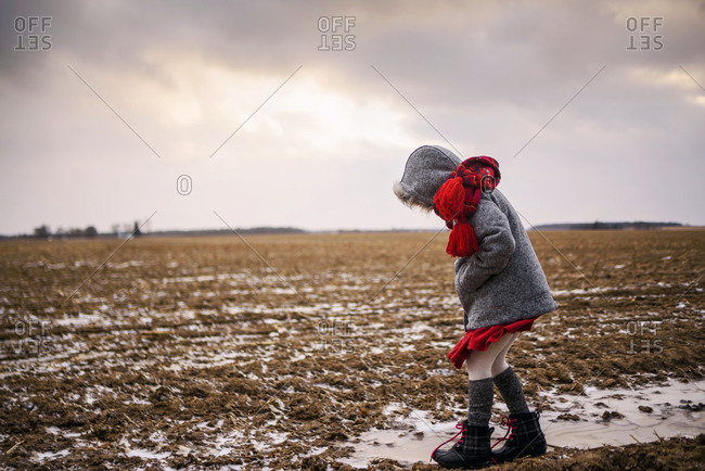 Young girl plays outside in the cold winter